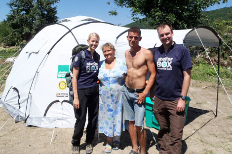 From left to right: Eva Doerr (DE), Elvira, Stas, Andrew Clouting (AU), standing infront of Elvira and her son's new temporary home in flood-hit Nizhnebakanskaya, Russia, July 2012.