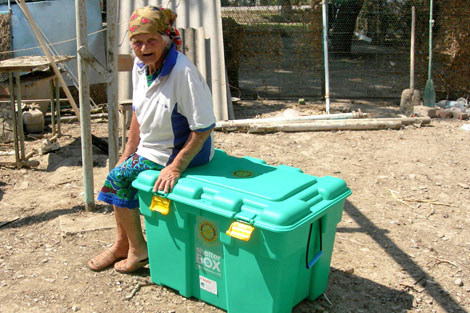 Lisanova with her ShelterBox on her land, Russia, July 2012.