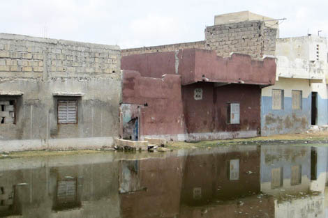 hotograph shows the flood damage made to the buildings in Dakar, Senegal. The dark shadowed line across the buildings show how high the floodwaters were - over one metre, September 2012.