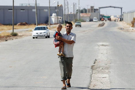 A man carries his daughter as he walks in Bab Al-Salam refugee camp in Azaz August 29, 2012. Photograph taken by Reuters/Youssef Boudlal, courtesy the Thomson Reuters Foundation – AlertNet.