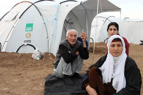Abrahim and Zakha Khalo with their granddaughter Zozan outside their ShelterBox tent at Domiz refugee camp, Iraq Kurdistan, November 2012.