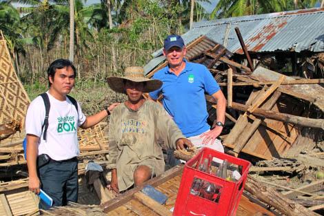 Volunteer Alfrancis Verdida (far left) with SRT member John Cordell (US) (far right) talking to a typhoon survivor, Mindanao, Philippines, December 2012.