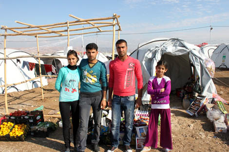 Customers outside of Naif's shop, a Syrian refugee who is using his ShelterBox tent not just to shelter his family but to also make a living, Domiz camp, Iraq Kurdistan, November 2012.