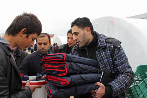 Solidarités International staff distributing a winter kit to a displaced Syrian family. Each time a kit is distributed, a member of staff registers the family's name and explains the contents of the kit, Al-Salameh camp, Syria, December 2012.