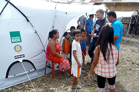 ShelterBox Response Team member Bjorn Andersson (SE) with beneficiary Analyn Cabiling as she receives her tent, Philippines, 2013.