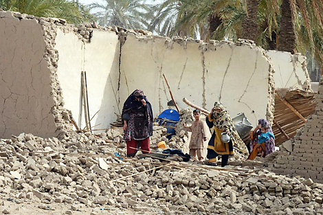 Photo coutersy of Balochistan Rural Support Programme (BRSP). Quake survivors walking amongst remains of their home, Mashail, Pakistan, April 2013.