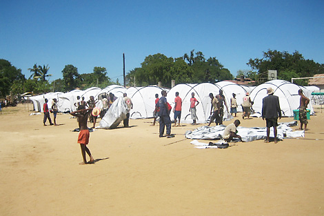 Displaced families in Madagascar receiving ShelterBox tents and helping setting up the camp in Toliara, March 2013.