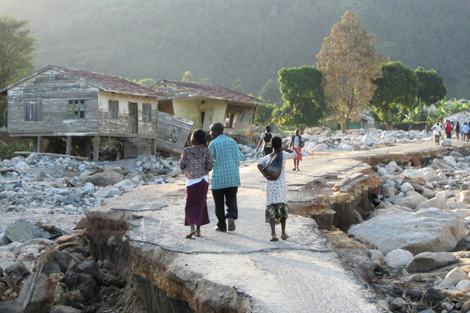Families looking at the remaining rubble in the Kasese region, Uganda, following recent floods, May 2013.
