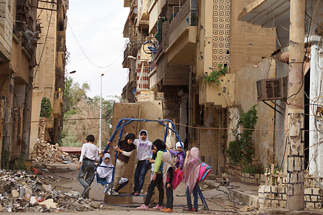 Girls play on a swing in a damaged street full of debris in Deir al-Zor, Syria, May 2013. Credit: Image courtesy of REUTERS/Khalil Ashawi.