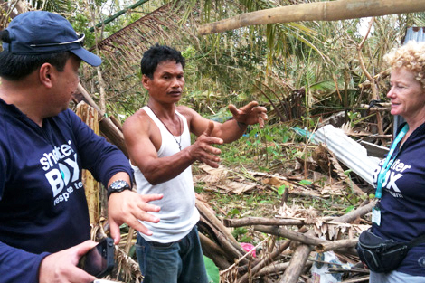 SRT members Abner Tayco (PH) and Liz Odell (UK) speaking to one of thousands affected by Typhoon Utor, Philippines, August 2013.