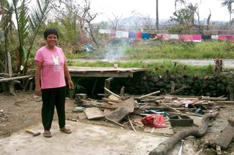 Mrs. Zaliver Baranguy Lual standing where her home and store used to be before the storm hit, Casiguran, Philippines, August 2013.