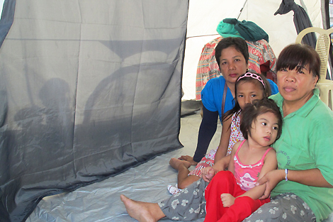 Evangeline with her daughters and sister in their new midi tent, Philippines, September 2013.