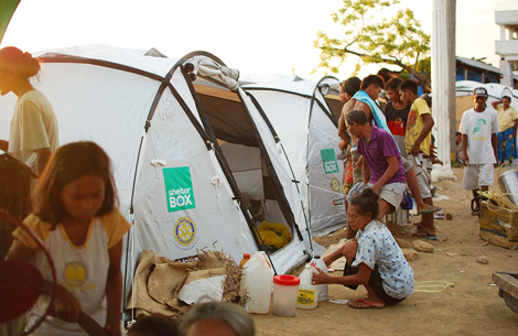Families forced from their houses by conflict set up ShelterBox tents, which will be their new homes for now, Zamboanga City, Philippines, September 2013.