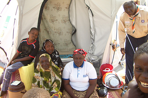 The Tsimbsno family outside their new tent, who had been living in cramped conditions in a school for 3 weeks, with the Niamey Scout Leader on the right, October 2013.