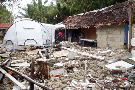 A ShelterBox tent amongst the rubble of Lamberto's house, The Philippines.