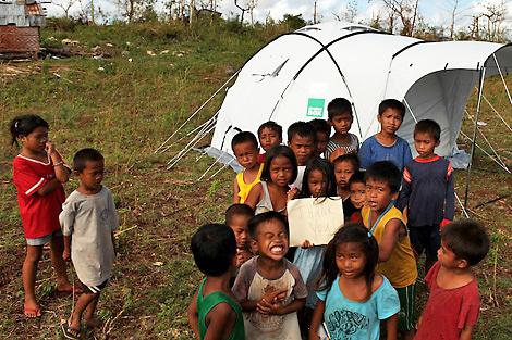 Children happy with their new homes in Machumben, Bantayan Island, Philippines, November 2013.