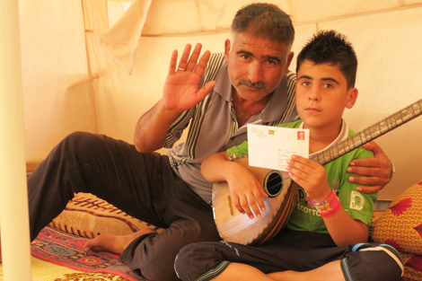 Delan with his father and the letter Toby wrote to him, Qushtapa refugee camp, Iraqi Kurdistan, October 2013.