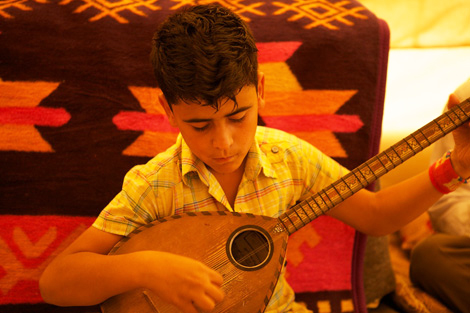 Delan playing his tambur at Qushtapa refugee camp, Irbil, Iraqi Kurdistan, October 2013.