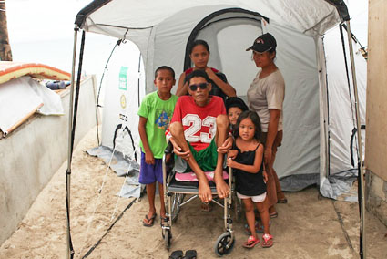 A family outside their ShelterBox tent, Guintacan island, Philippines, November 2013.