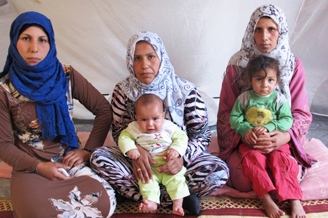 Ahed Hussein Zeidan (middle) holding her baby, Omar, in her ShelterBox tent with her two sisters either side and niece, Akaar, Lebanon, November 2013.