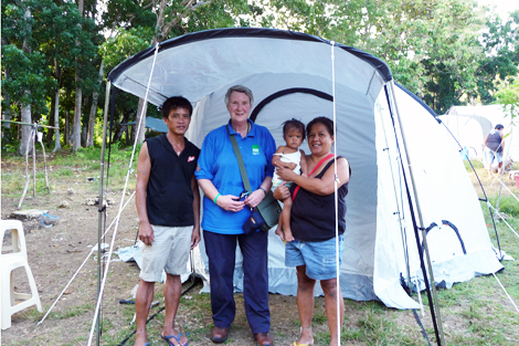 Response Team volunteer Sue Nelson with a beneficiary family in front of their new tent, Bohol, Philippines, November 2013.