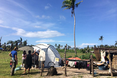 ShelterBox Response Team member Anne Seuren (NL) helping a family with their ShelterBox tent on Kinatarcan Island, Philippines, January 2014.