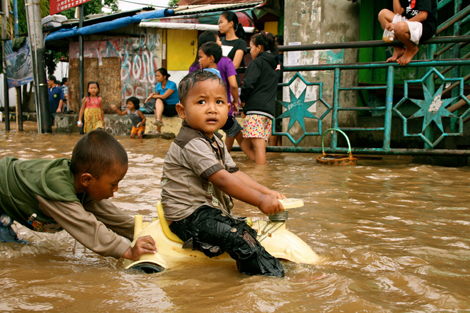 Photo by Kate Lamb. Children play in floodwaters in last year's floods in Jakarta, January 2013.