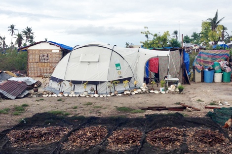 Families on Kinatarcan island make the most of their ShelterBox tents and remaining surroundings, Philippines, January 2014.