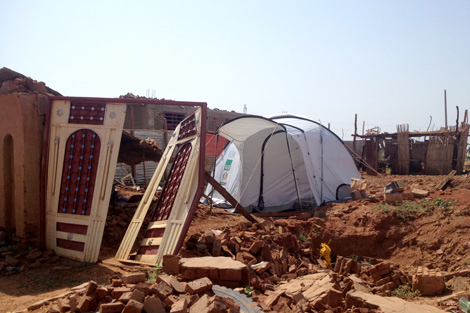 A ShelterBox disaster relief tent amongst the remains of a house leftover from the flooding, Sudan, August 2013.