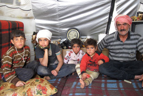 Syrian refugee Farouk Abdallah with his four sons in their ShelterBox tent, Bekaa Valley, Lebanon, November 2013.