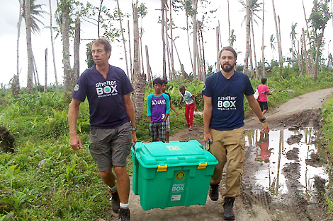 SRT volunteers Owen Smith (left) and Phil Wheeler (right) carrying the Tragura's ShelterBox to where their isolated home once stood, Leyte, Philippines, February 2014.