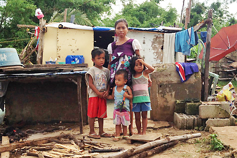 Jeresita with her three young children, including her youngest Elzed holding the hammer who is trying to help rebuild their house that is pictured behind them, which was damaged by Typhoon Haiyan, Kinatarcan island, Philippines, January 2014.