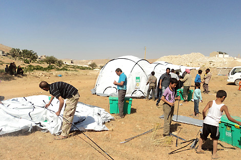 LEBANON. October 2013. Syrian refugee families setting up tents distributed by one of ShelterBox's partners. (ShelterBox)
