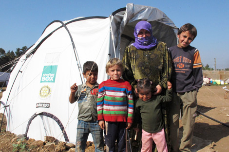 AKAAR/LEBANON. November 2013. 42-year-old Anna Al Naser with her children in front of their ShelterBox tent. She said, 'My hope is only for my children to be safe and we go back to our home country... and that the shelling stops.' (Rebecca Novell/ShelterBox)