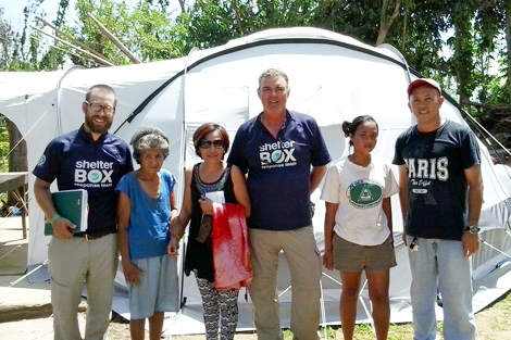 Three-generational female family infront of their new shelter with Response Team members Matt White (UK-left) and Gary Bidner (AUS-centre) with local contact Raymond Burnas (right).