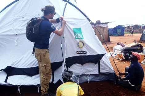 ZIMBABWE. 12 APR 2014. ShelterBox Response Team member, Phil Wheeler (UK), helps to set up a disaster relief tent in the Chingwizi camp. (Sharon Donald/ShelterBox).