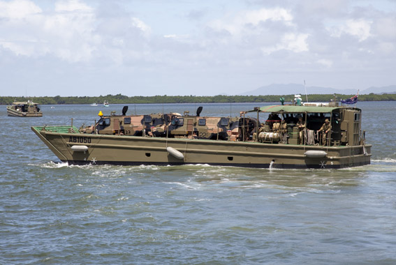 Bushmaster vehicles belonging to the 2 Royal Australian Regiment are transported ashore by landing craft.