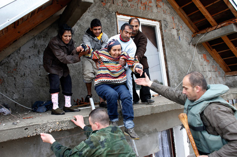 OBRENOVAC, SERBIA. 16 MAY 2014. Serbian army soldiers evacuate people from a flooded house in the town of Obrenovac, southwest of Belgrade. Image courtesy of REUTERS/Marko Djurica.