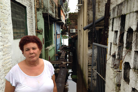 Paraguay 9 July 2014. Estelvina Gonzales, mother of three, is one of 15 people living in a church along the embankments of Asunción. The roof of Estelvina's house can be seen behind her at the end of what was once a street. The water has reached the foundations of the church. When asked where her and her children will go, Estelvina told us that she did not know. (Liz Odell/ShelterBox).