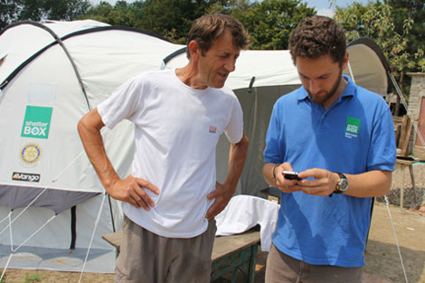 Serbia July 2014. ShelterBox response team member Sam Hewett using the new phone app to gather information from a recipient of ShelterBox aid. (Rachel Simpkins/ShelterBox).