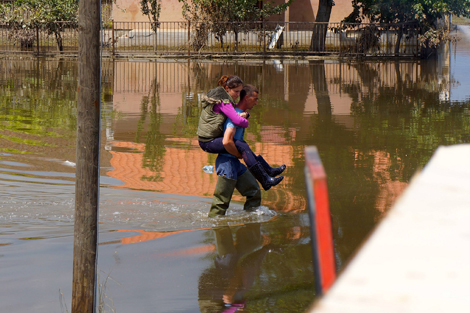 SERBIA. MAY 2014. Young couple in Serbia wade through flood waters that have not receded weeks later. (Torstein Nielsen/ShelterBox)