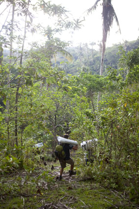 SRT member, Harry Roberts carries poles for a relief tent deep into the rainforest in Gabawan, Albay, Philippines