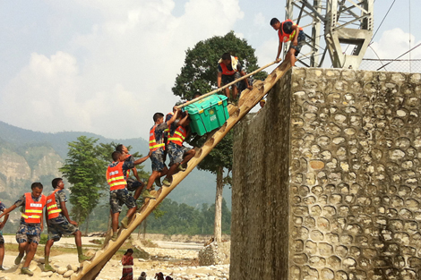 Members of the Nepal police hauling ShelterBoxes onto a damaged bridge in Taranga, Surkhet District, Nepal. Photo: Sanchia Gallagher/ShelterBox.