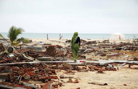 Indonesian woman walk amongst the destruction of Ache