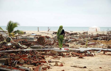 Indonesian woman walk amongst the destruction of Ache