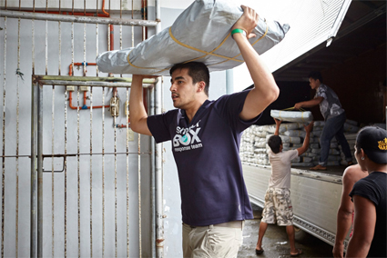 Response team member Richard Loat unloads a delivery of tarpaulins, which will be used to create shelters and repair structures, in Eastern Samar in the Philippines. Image courtesy of Liam Norris.