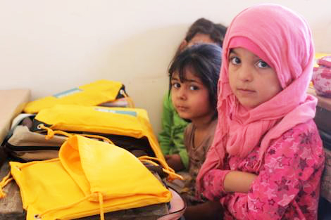 Syrian children in a classroom, receive ShelterBox school packs