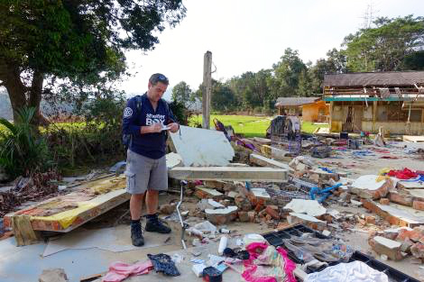 ShelterBox response team member Ben Julian standing in the remains of a house devastated by flooding in Pahang, Malaysia