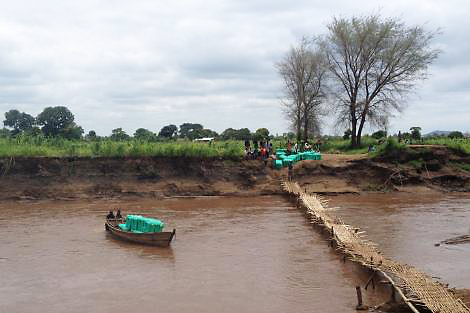 ShelterBox response team members are helped to transport ShelterBoxes over a large river in Malawi by boat, rather than risk the fragile bridge. (ShelterBox/Rebecca Swist)
