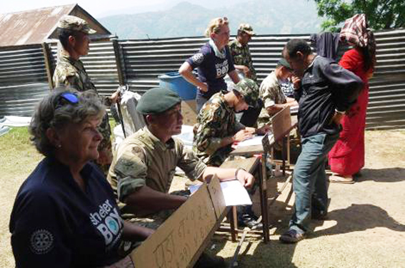 Response team members Sallie Buck (left) and Becky Maynard (centre) work alongside Gurkha soldiers to distribute aid in Nepal